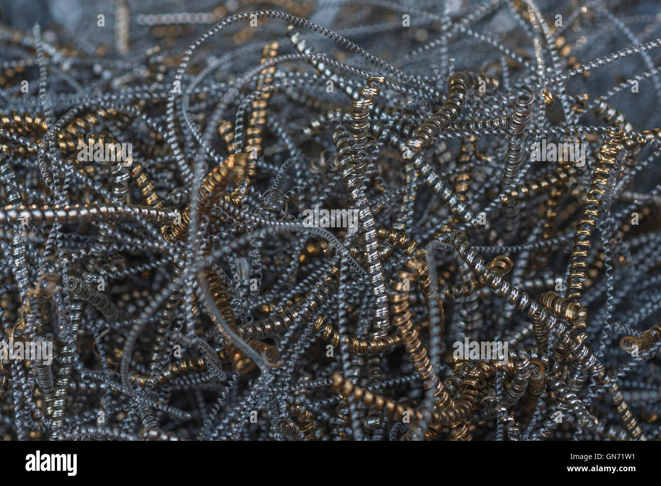 Close shot of metal turnings / industrial swarf from CNC machining operations. Industrial waste, metal waste. Spiralling - Stock Image