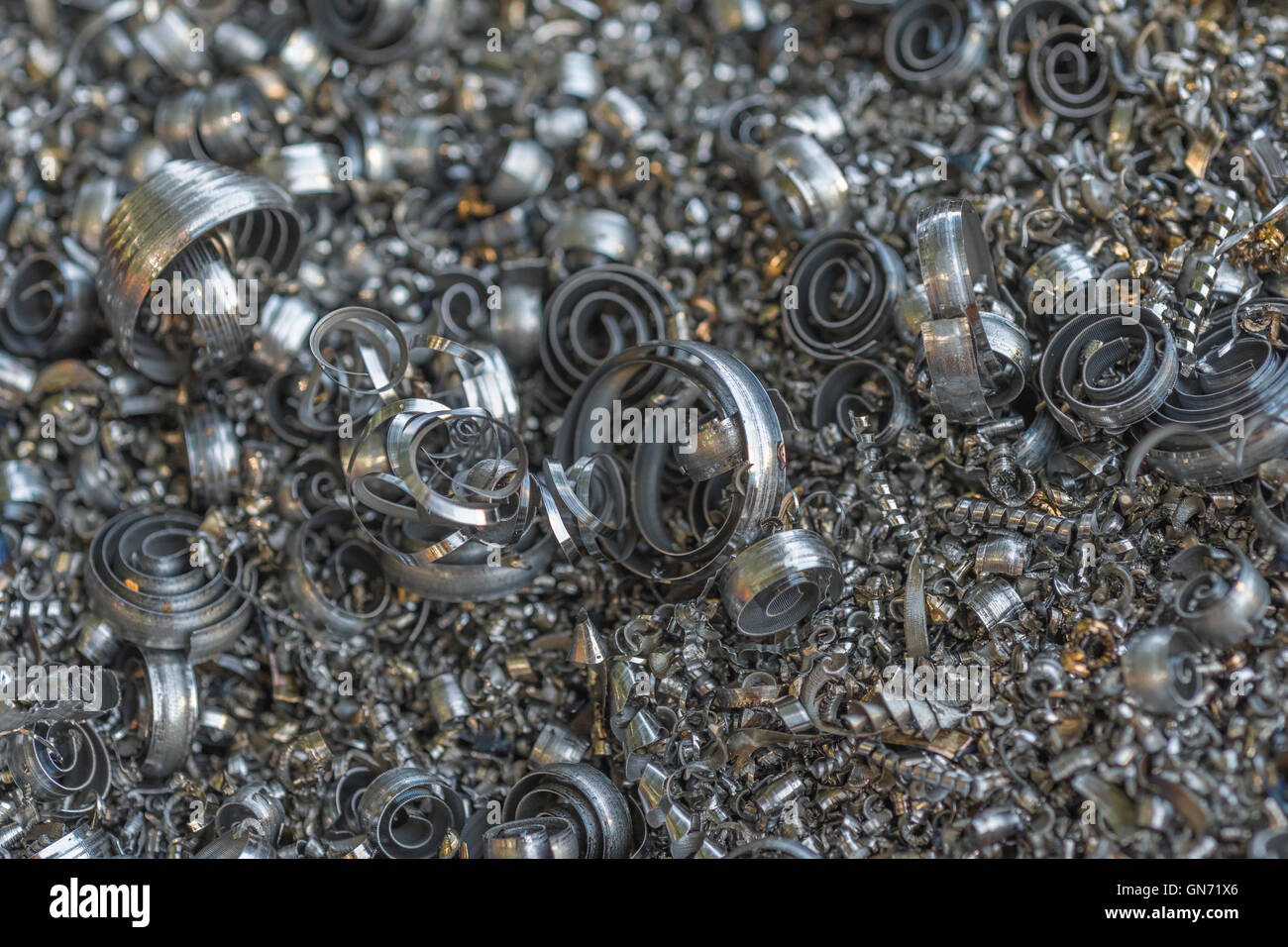 Close shot of metal turnings / industrial swarf from CNC machining operations. Industrial waste, metal waste. - Stock Image