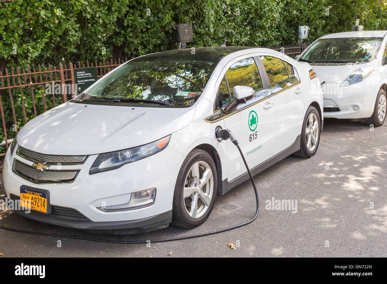 A New York City Parks department Chevy Volt electric car receives a charge at a charging station in Central Park. Stock Photo