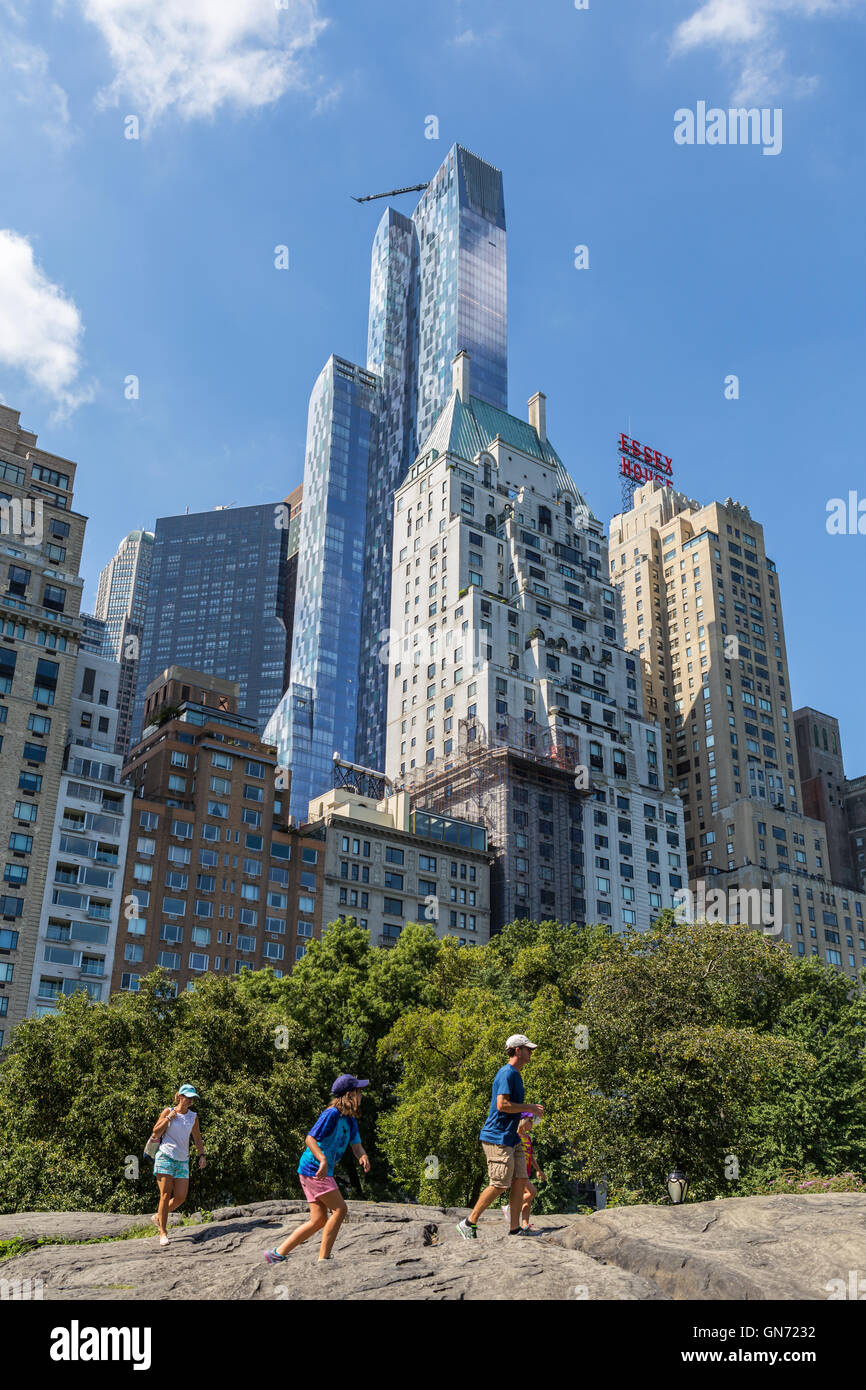 Residential skyscraper One57 towers over a family climbing on rocks in Central Park and other nearby buildings on - Stock Image