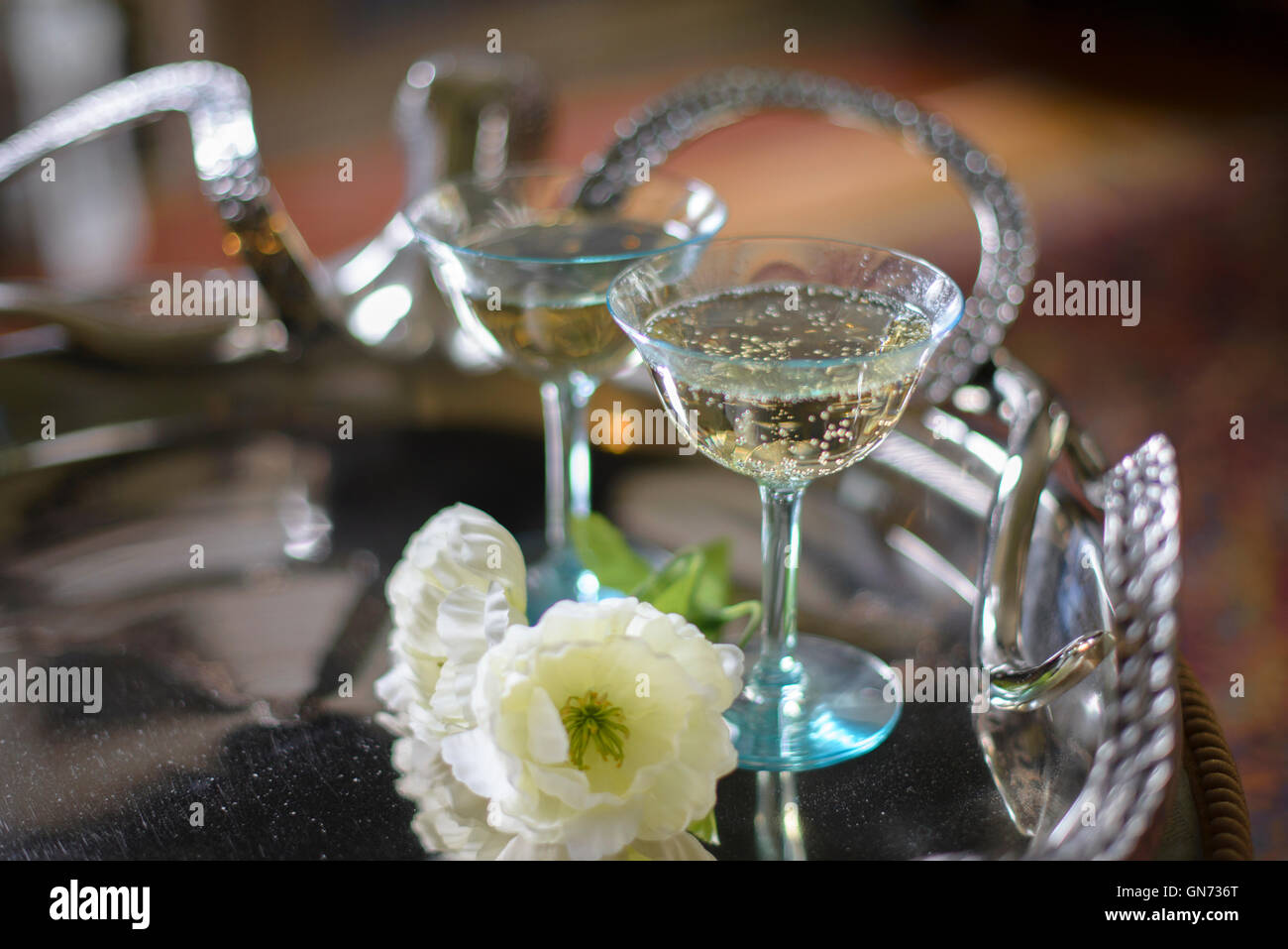 Champagne glasses on a silver serving tray - Stock Image