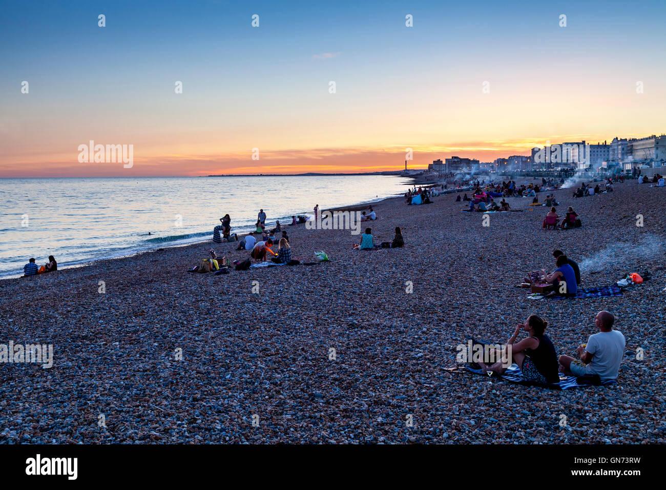 People Sitting On Brighton Beach At Sunset, Brighton, Sussex, UK - Stock Image