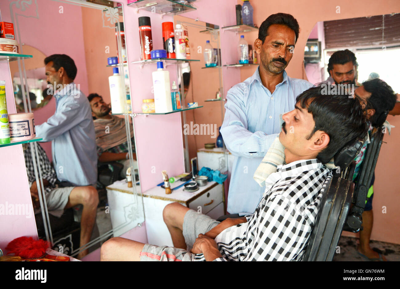Hairdresser shaving a man is the streets of Delhi,India Stock Photo