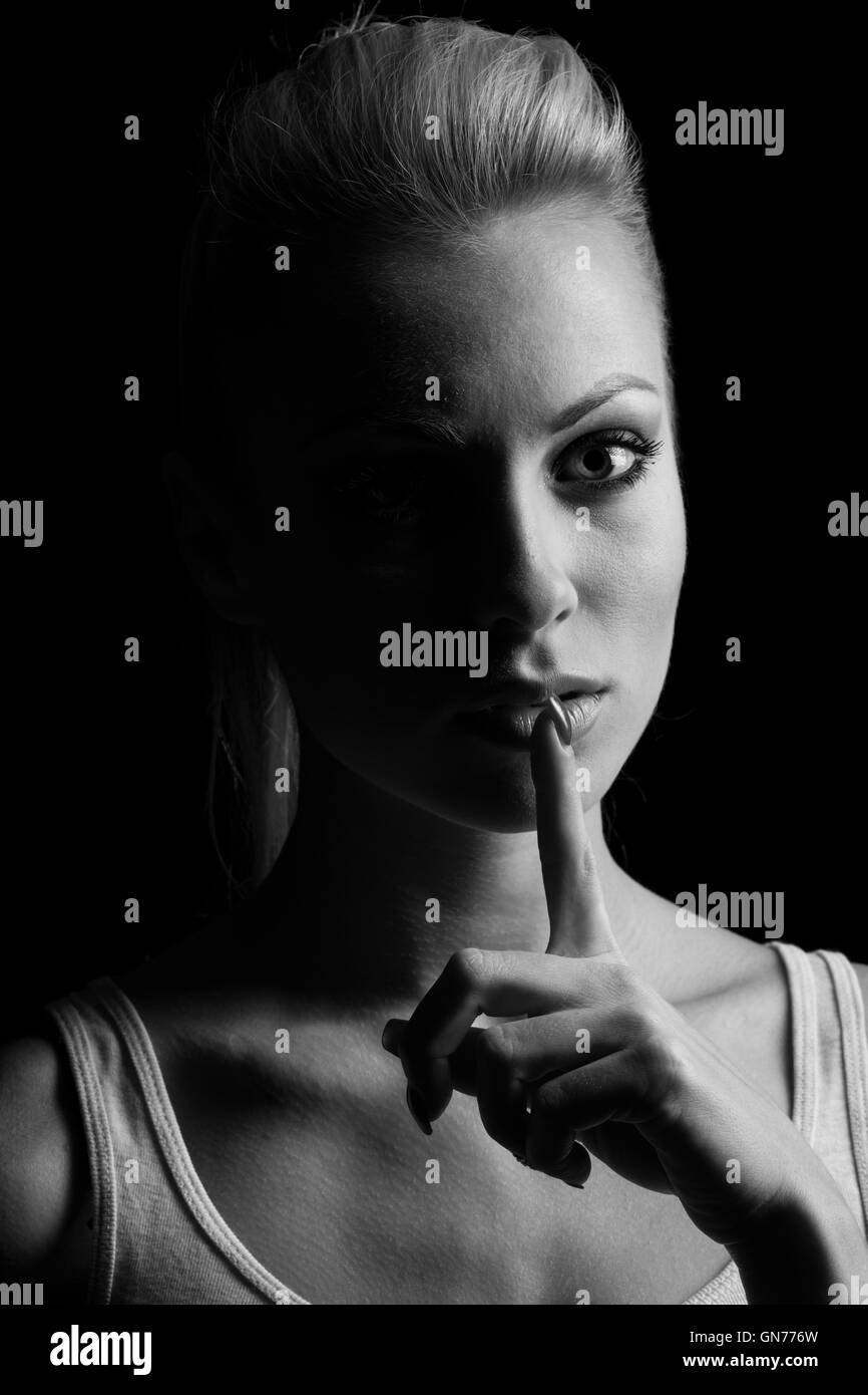 Mystery woman in shadow with finger on lips gesturing silence. Dark portrait. Stock Photo