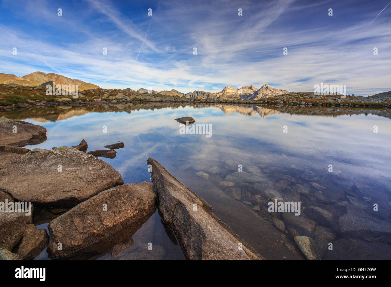 Peaks are reflected in Lake Bergsee at dawn Chiavenna Valley Spluga Valley Switzerland Europe - Stock Image