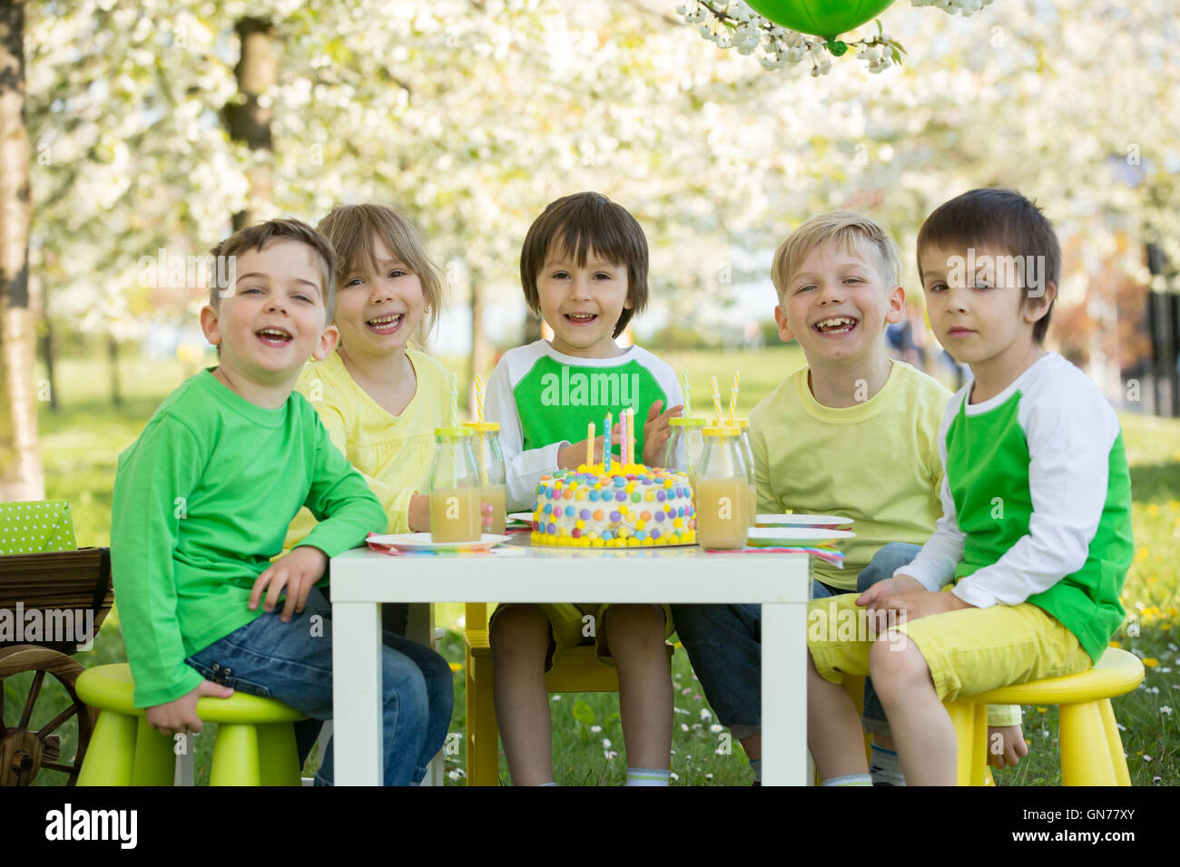 Happy sweet preschool children, friends and relatives, celebrating fifth birthday of cute boy, outdoor in blooming - Stock Image