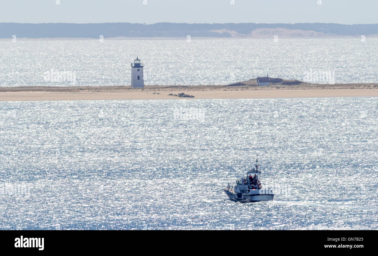 A whale watch boat carrying passengers travels in the Cape Cod Bay past a lighthouse. - Stock Image
