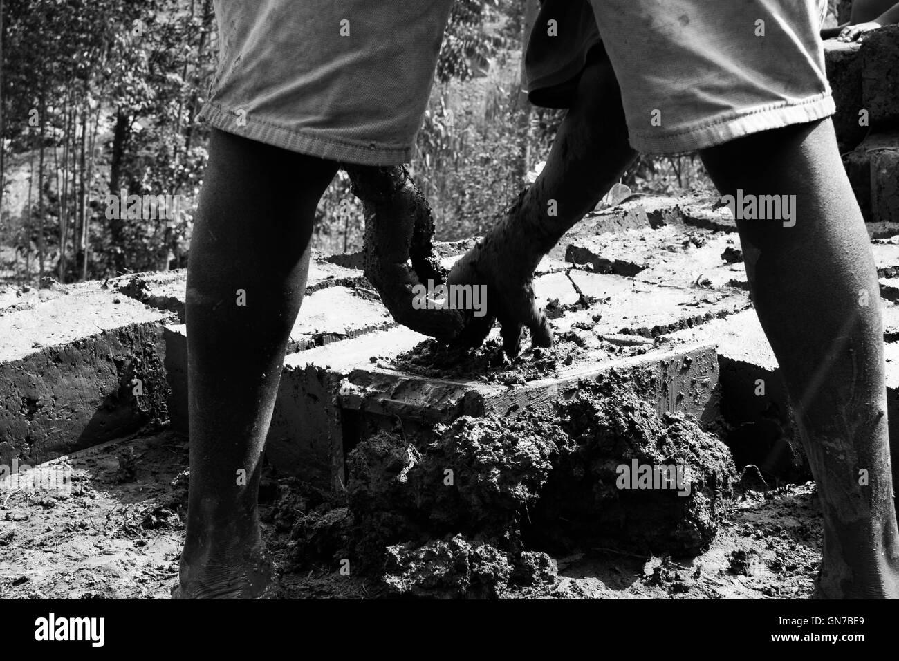 A Rwandese boy is making a mud brick - Stock Image