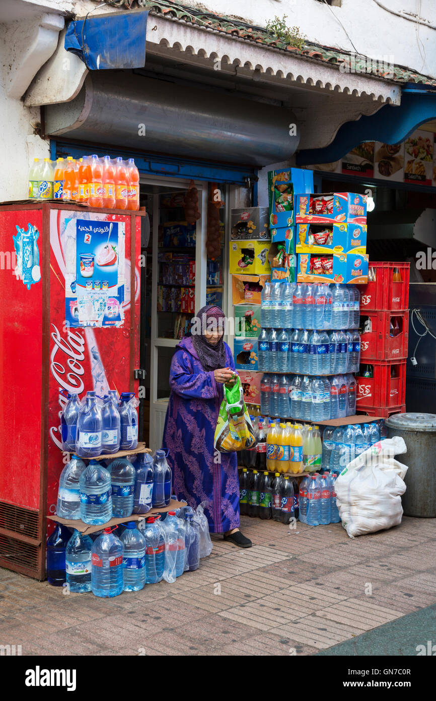 Essaouira, Morocco.  Woman Leaving Small Grocery and Sundries Shop.  Bottled Water Supplies around the Entrance. - Stock Image