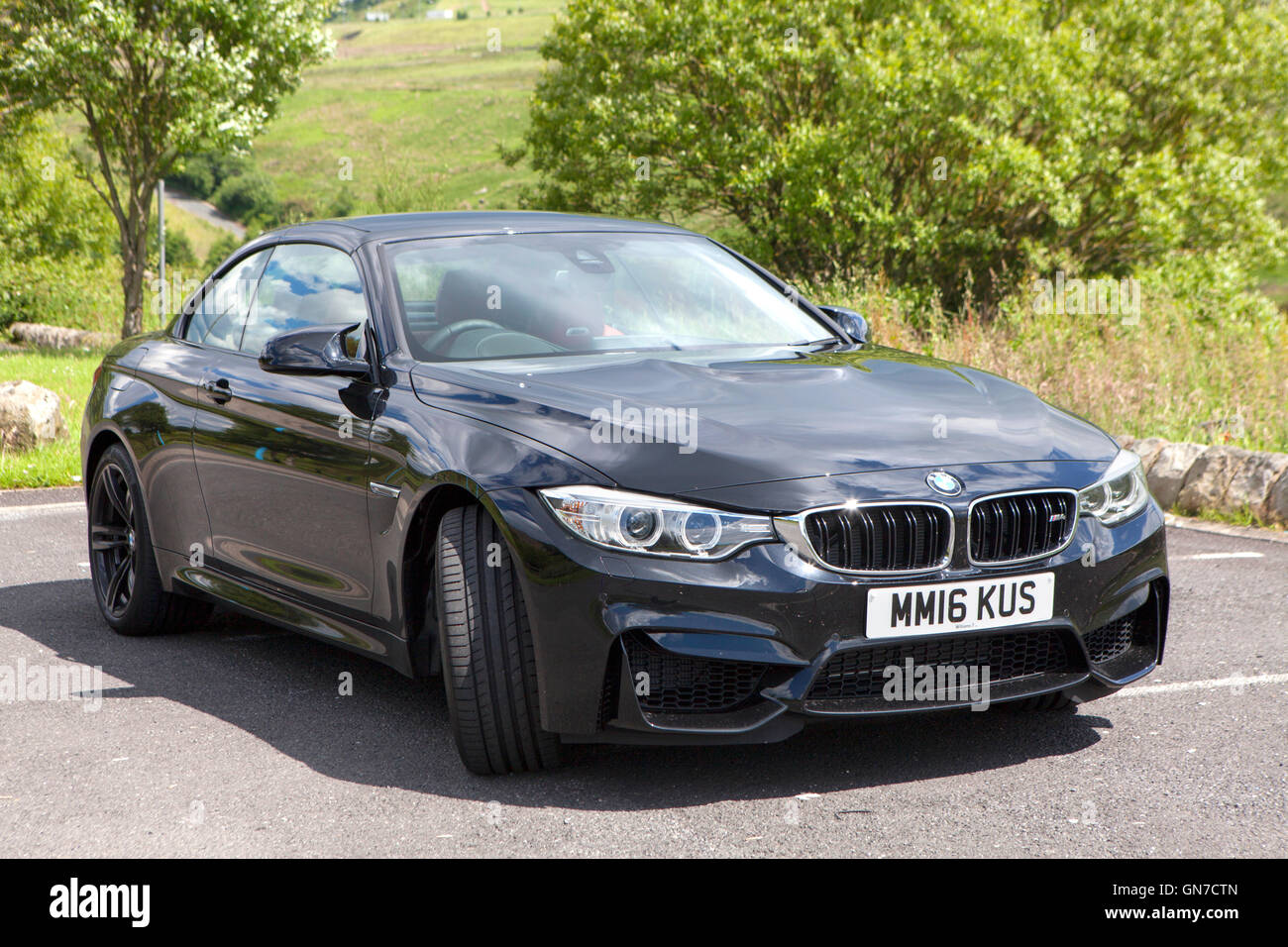F83 Black BMW M4 convertible 2 door coupe with red leather parked in the countryside in summer - Stock Image