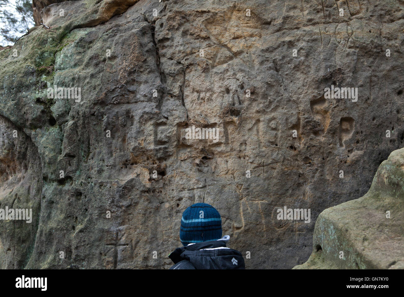 A boy looks at the graffiti carved by Soviet soldiers in 1945 and 1968 in the sandstone rocks in the forest outside - Stock Image