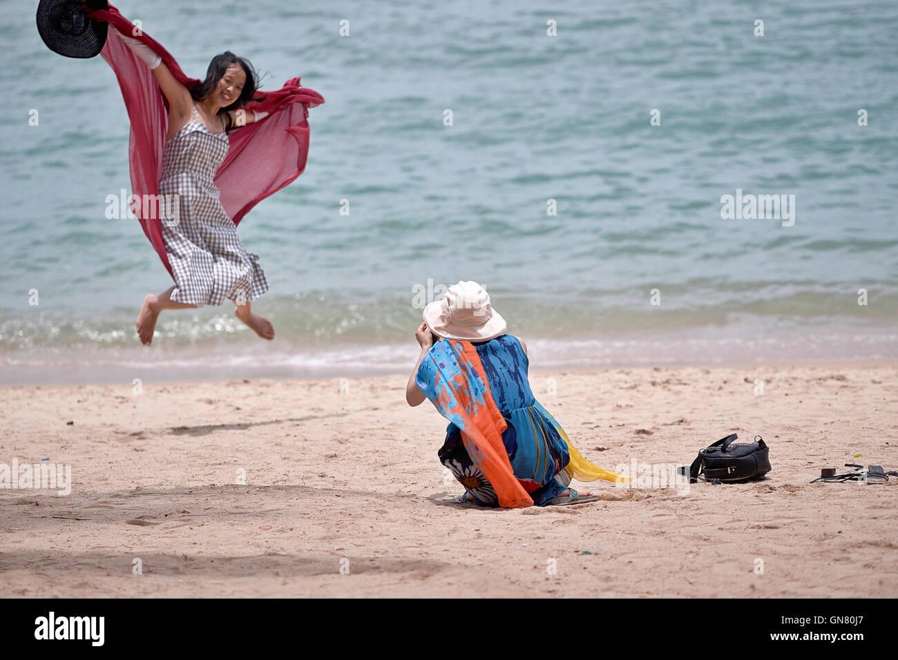 Female photographer shooting leaping female companion. - Stock Image