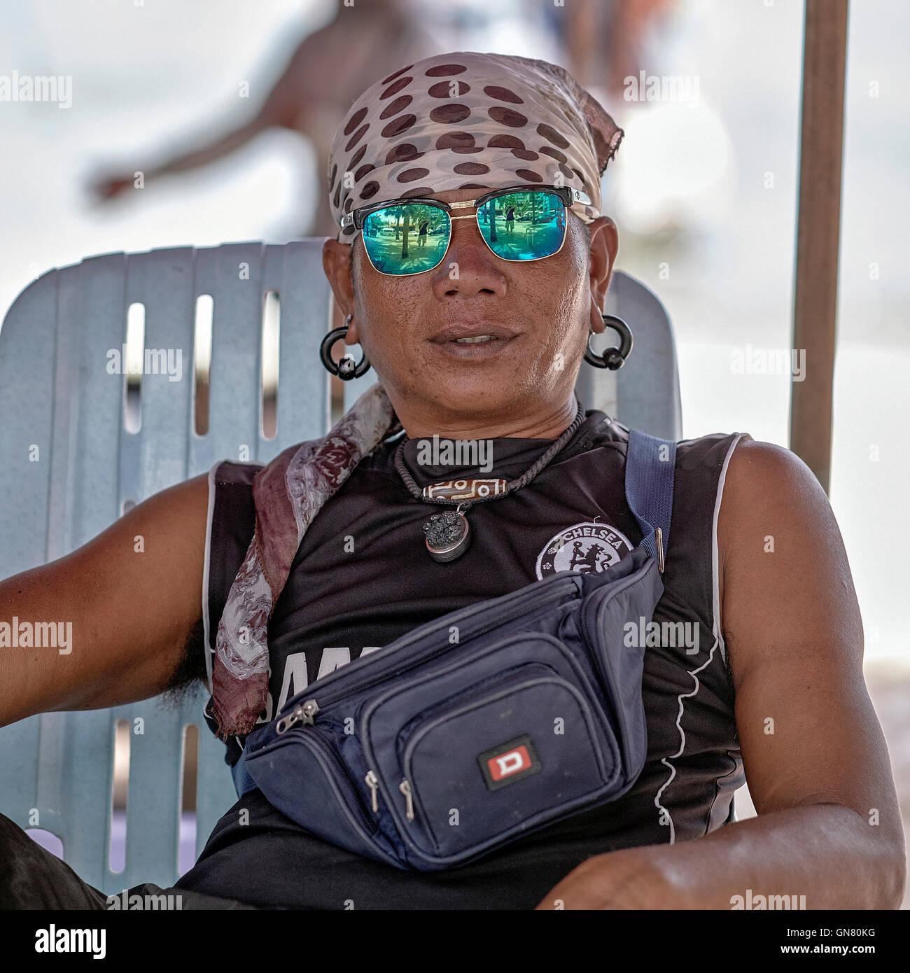 Thai man with green tinted Polaroid sunglasses. Thailand S. E. Asia. - Stock Image