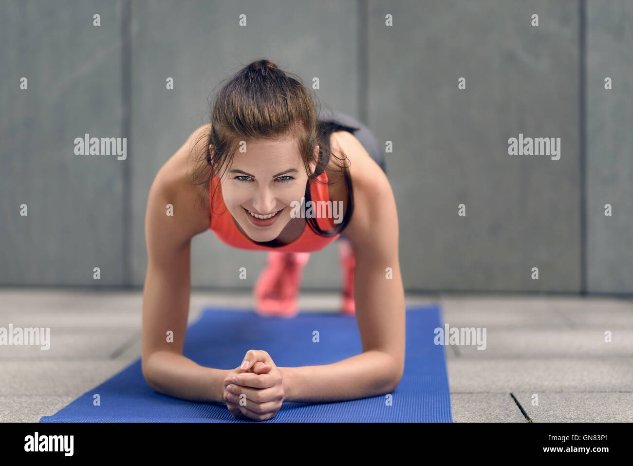 Fit young woman doing planks, strengthening her core, working out on a mat, lifestyle and health concept - Stock Image