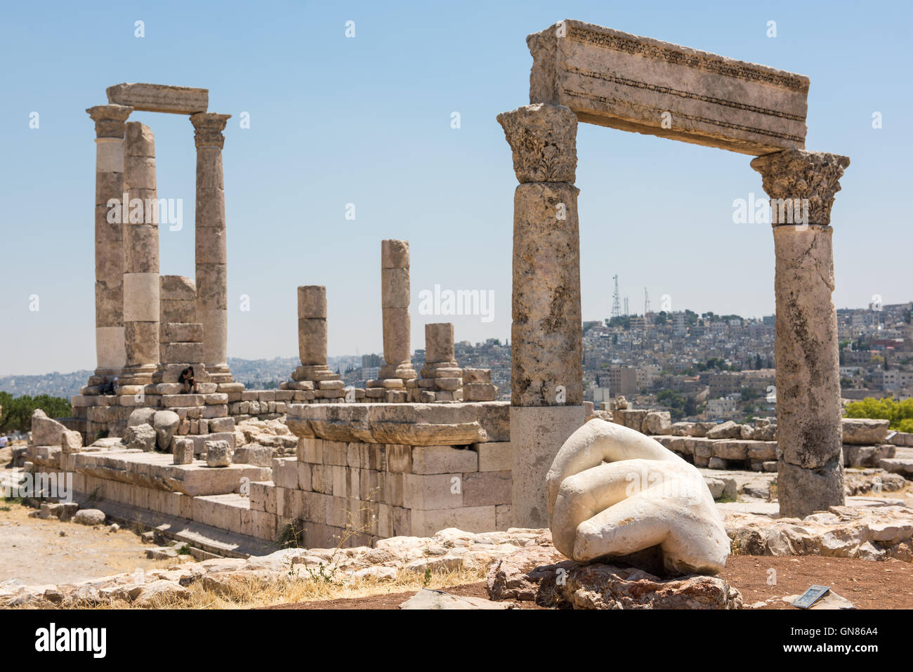 Ancient ruins of a roman temple in the Citadel of Amman. The hand of a statue in the foreground - Stock Image