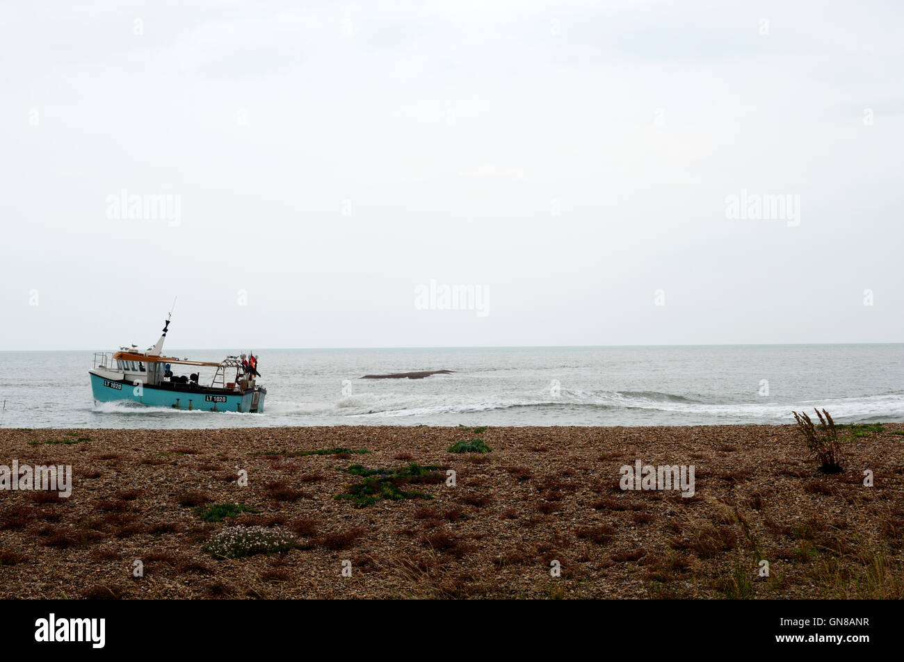 Fishing boat returning to Orford at the entrance to the river Alde, Shingle Street, Suffolk, UK. - Stock Image