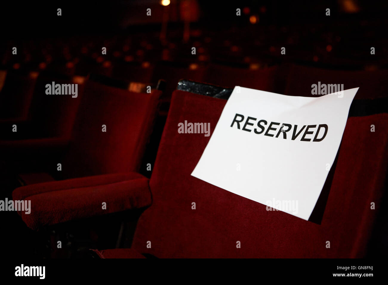 reserved sign on a seat in a row of seats in the stalls of an old style theatre - Stock Image
