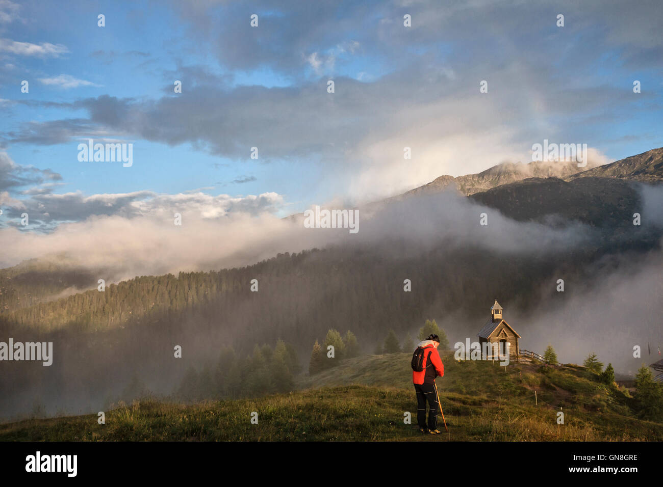 The Dolomites, Trentino, Italy. A walker pauses by the wooden chapel overlooking Passo di Valles  on the Alta Via - Stock Image