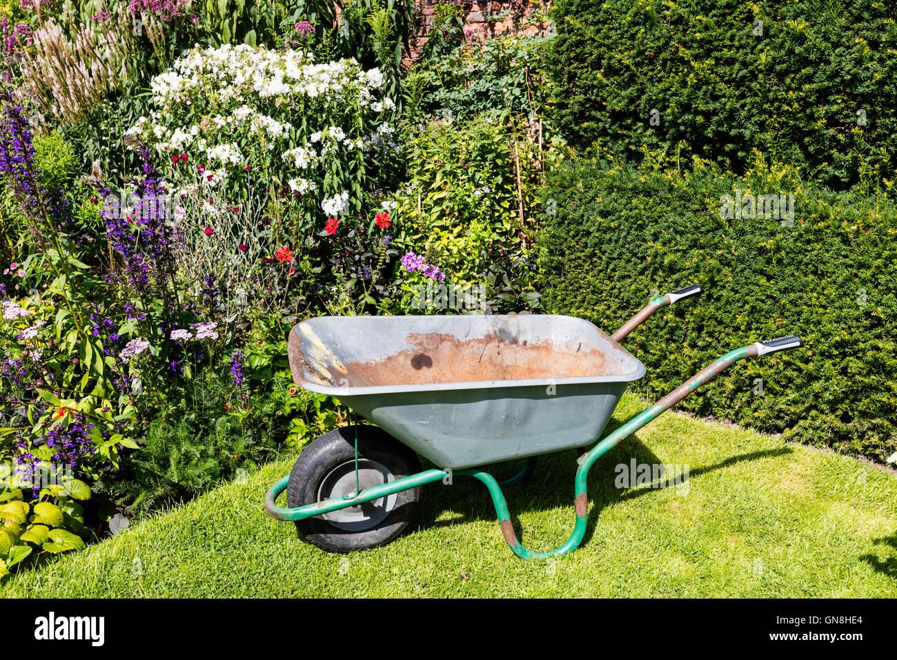 Old well used rusty wheelbarrow in a summer garden. - Stock Image