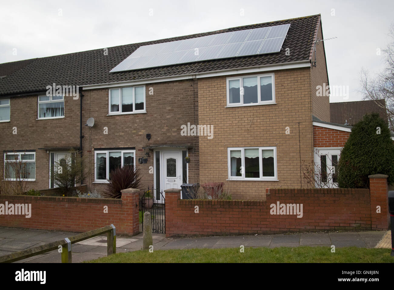 solar panels on the roof of an end terrace property on a housing estate on overcast day Liverpool Merseyside UK - Stock Image