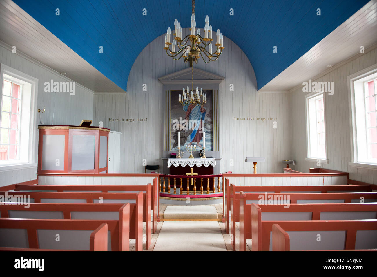 Inside the church of Arnafjordur on the Faroe Islands with benches and altar - Stock Image