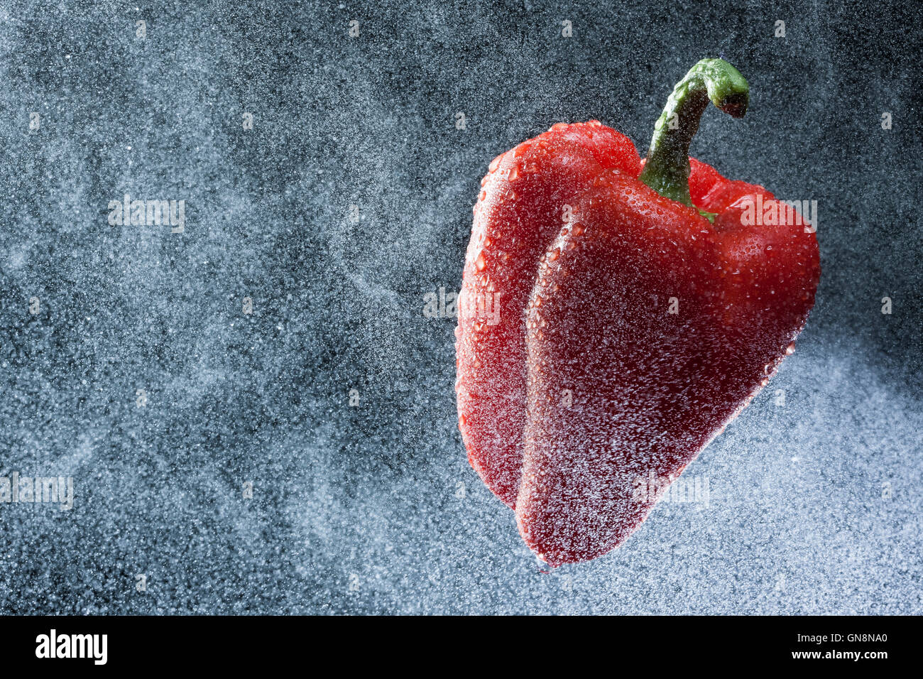 Red pepper in a spray against a black background. A series of fruits and vegetables in motion. Stock Photo