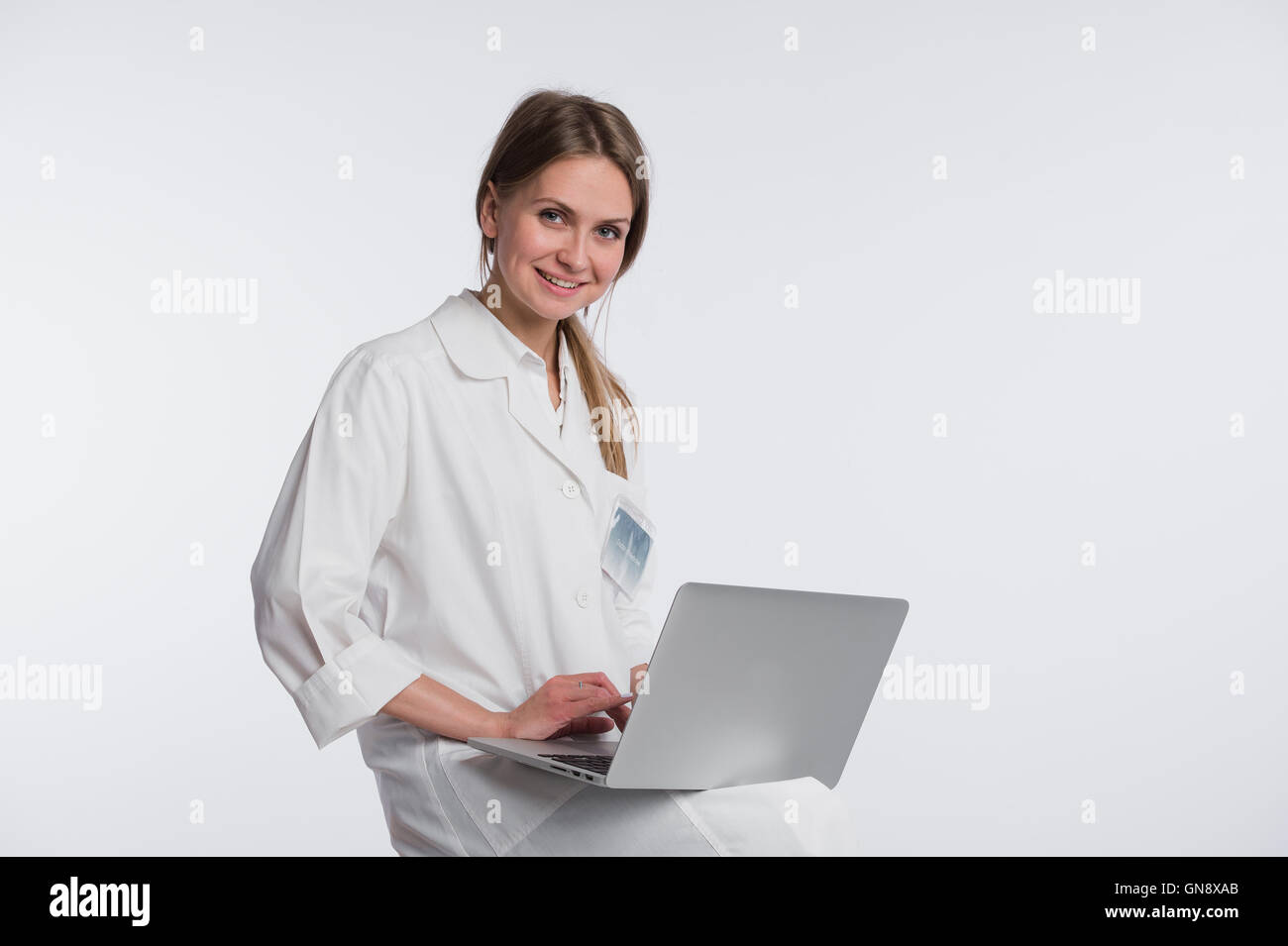 Smiling female doctor working on her laptop against a white background Stock Photo