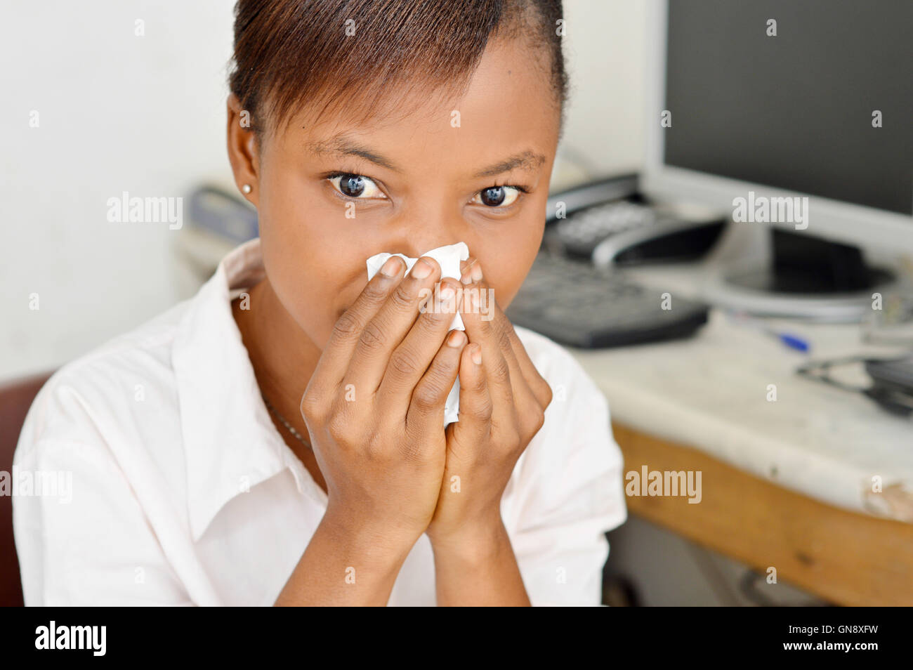 young woman has clogged her nostrils with her  handkerchief because they flow. - Stock Image