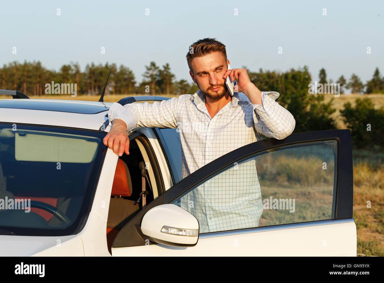 Young handsome man opened the door of his car. Man talking on the phone. Always connected. - Stock Image