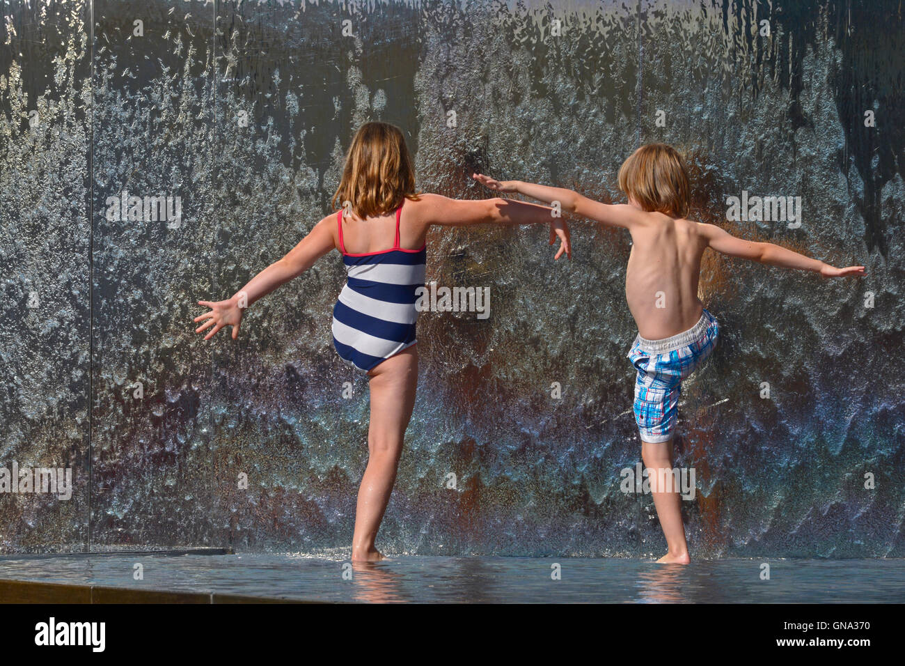 Bristol, UK. 29th Aug, 2016. UK Weather. Children doing Water Ballet in the fountains in Millennium Square in Bristol - Stock Image
