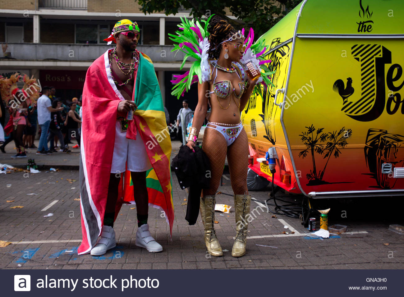 Man wearing flag with woman wearing carnival costume standing at the roadside during the 50th Notting Hill Carnival, - Stock Image