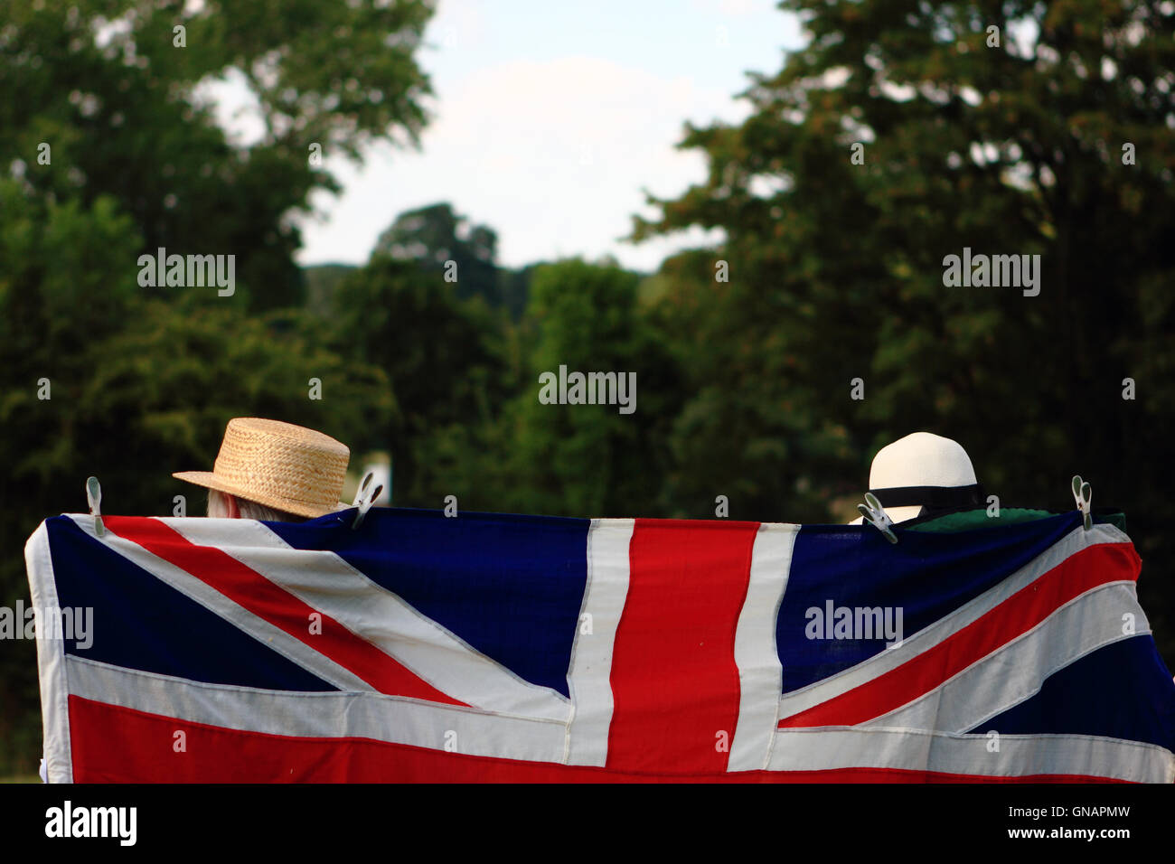 Two people sitting behind a union flag. Stock Photo