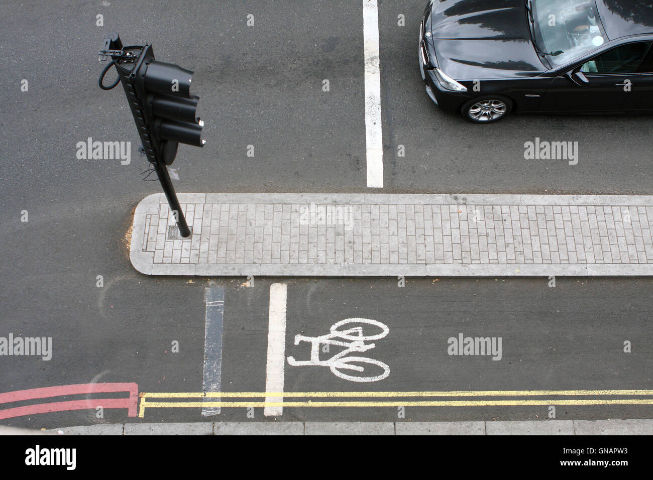 A vehicle waiting at a set of traffic lights next to an empty cycle lane in London, England. Stock Photo