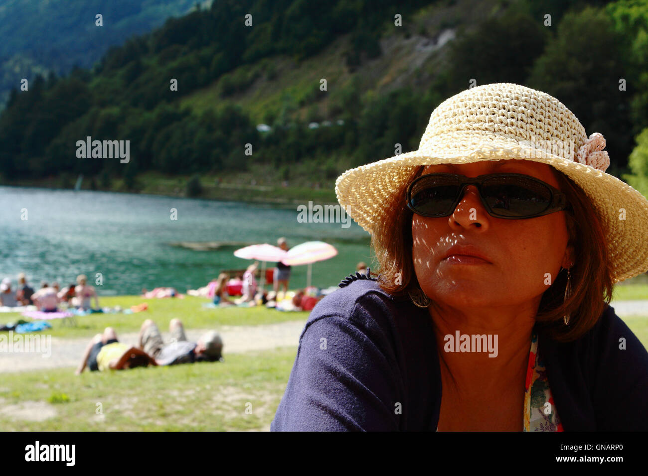 A female sitting in sunshine in the French Alps. A tree lined mountain, a lake and people sunbathing in the background Stock Photo