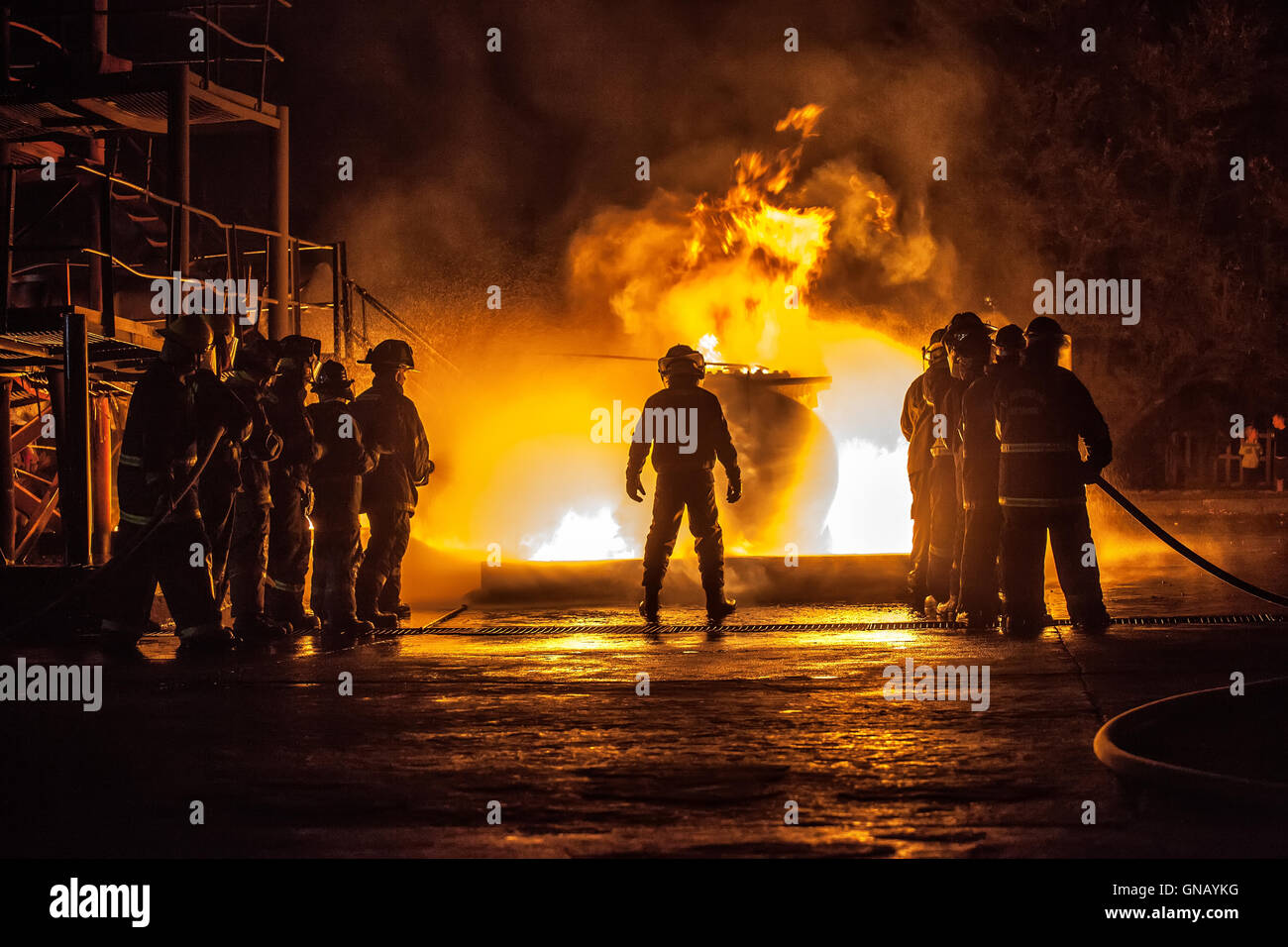 Firechief controlling two teams fighting a fire - Stock Image