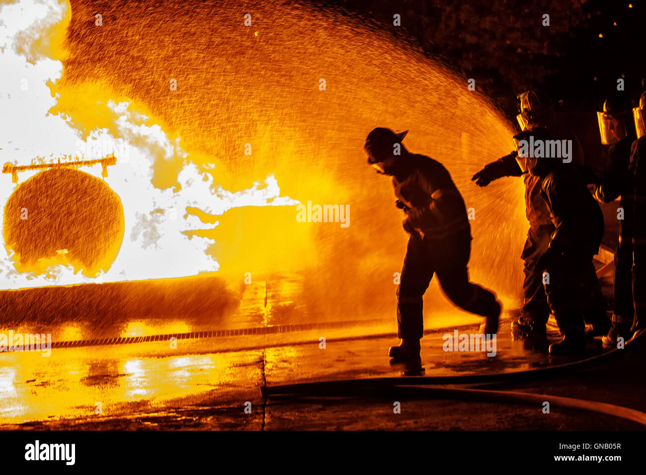Firefighter running towards fire - Stock Image