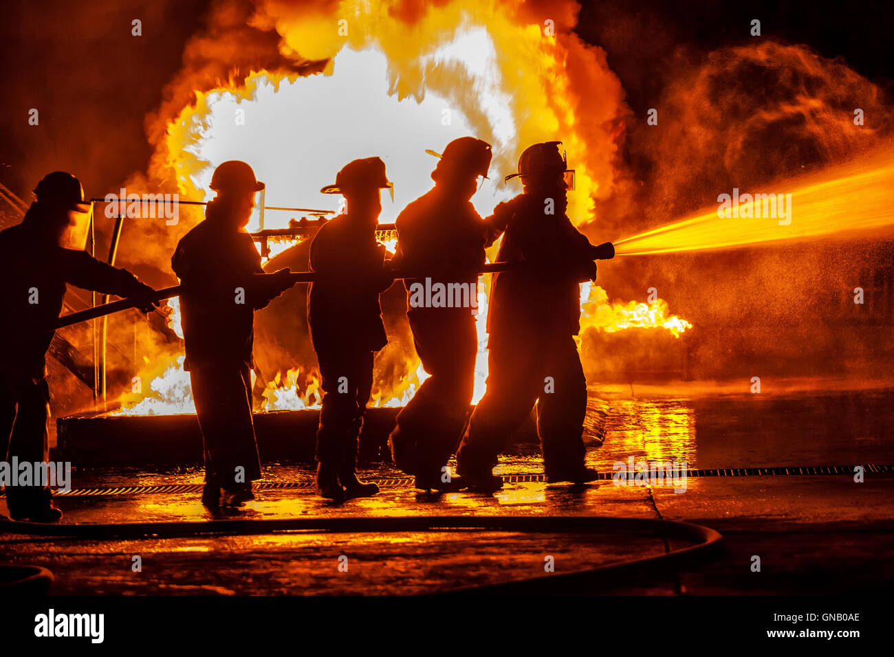 Group of firefighters moving towards fire with hose - Stock Image