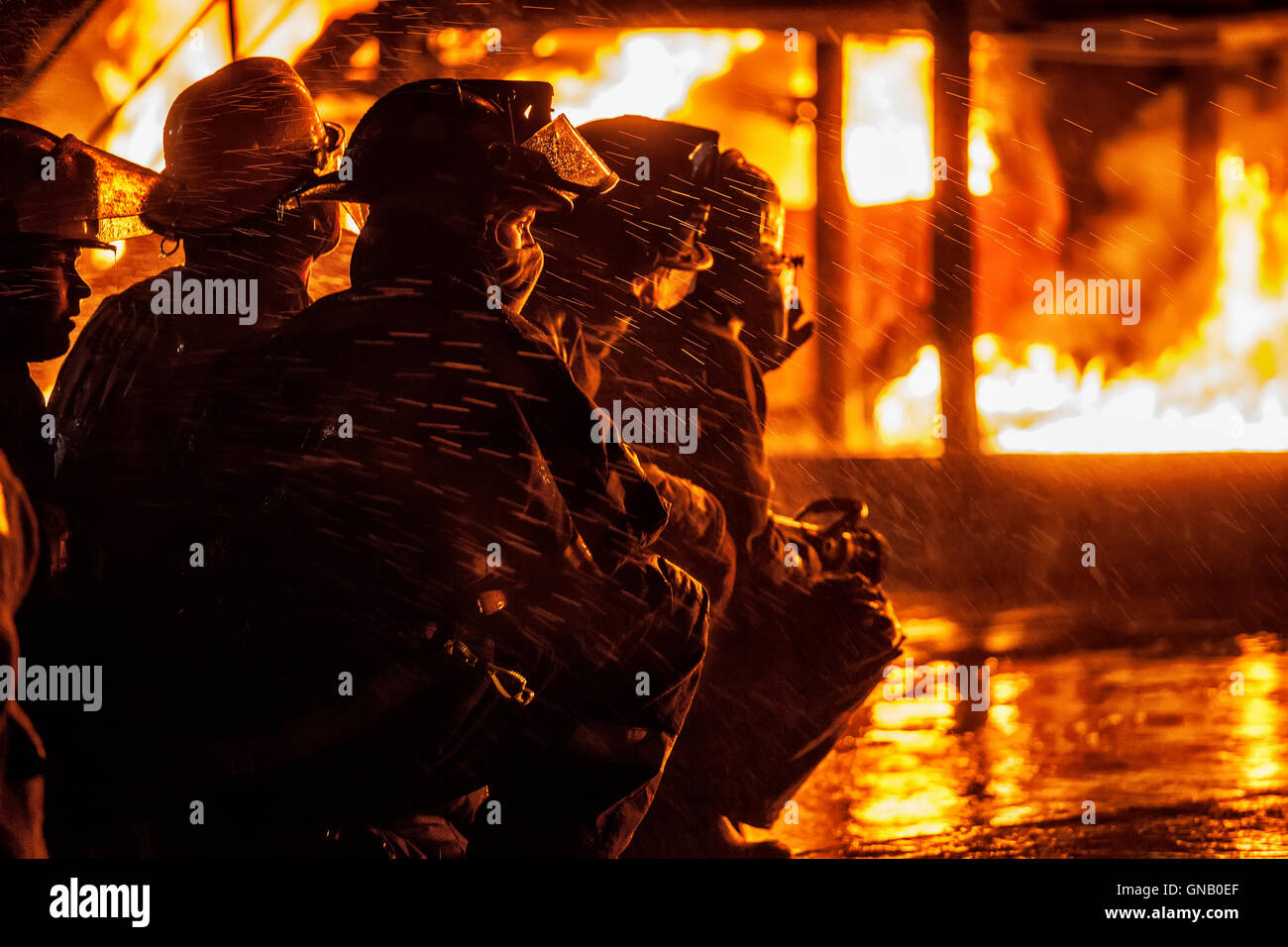 Group of firefighters observing fire - Stock Image