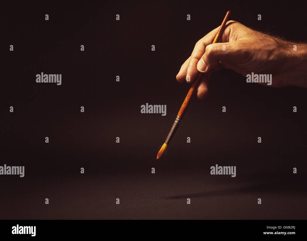 Conceptual composition, man's hand holding a brush on black background. - Stock Image