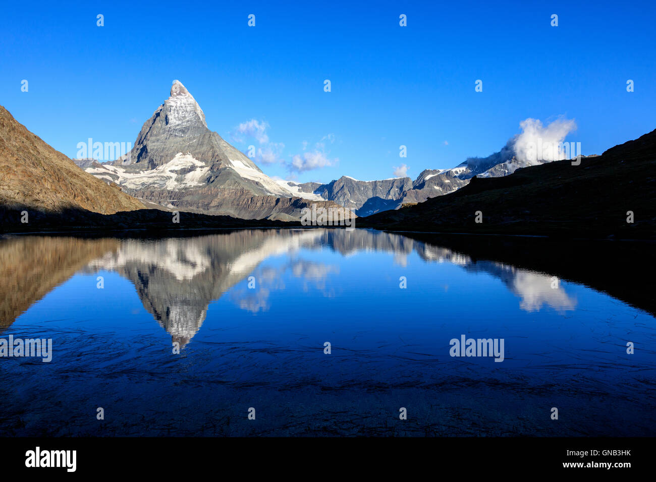 The Matterhorn reflected in the blue waters of Lake Stellisee Zermatt Pennine Alps Canton of Valais Switzerland - Stock Image