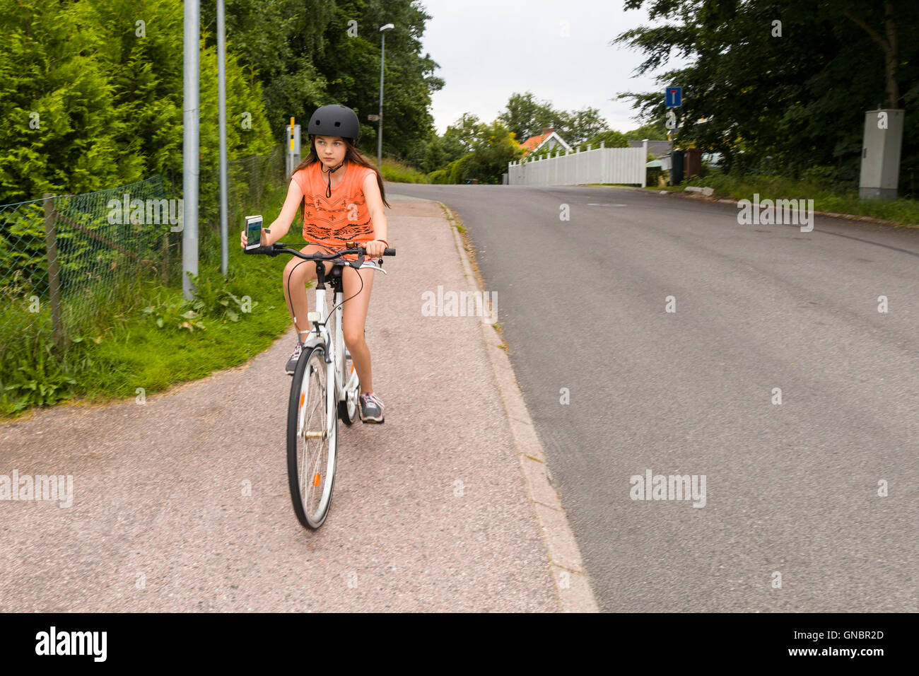 Teenage girl bicycling whilst Pokemon hunting with an iPhone smartphone - Stock Image