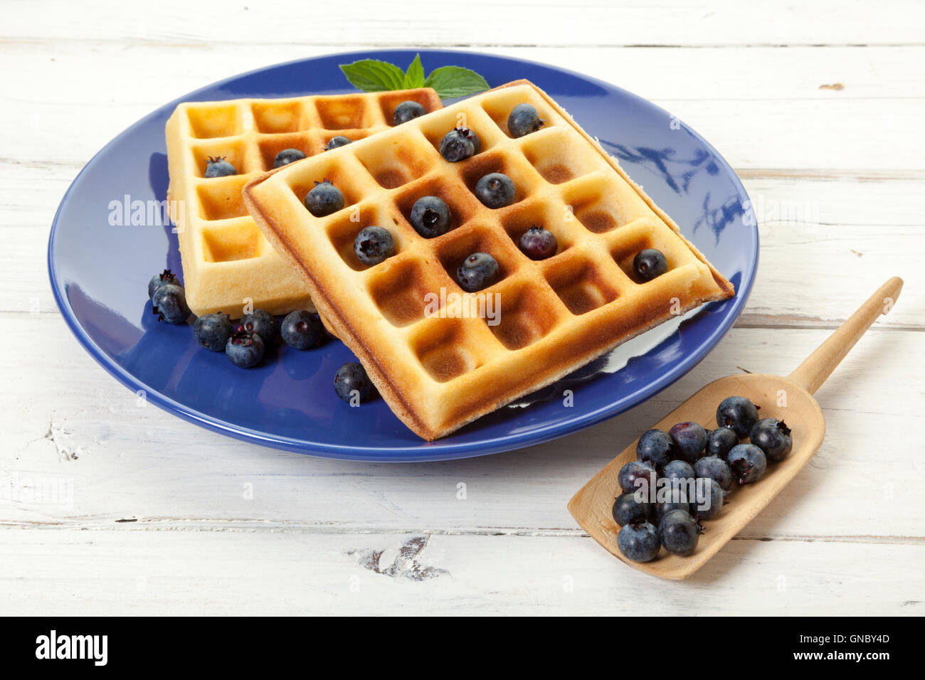 Belgian waffles with blueberries on blue plate, on rustic wooden table - Stock Image