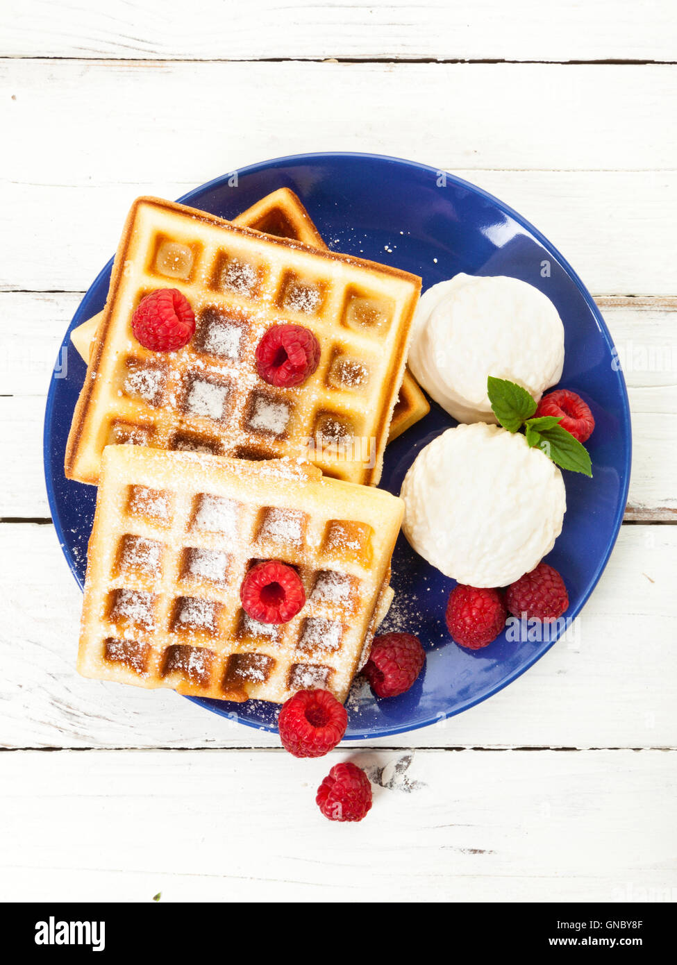 Belgian waffles with raspberries, vanilla ice cream scoops and powdered sugar on blue plate, on rustic wooden table, - Stock Image