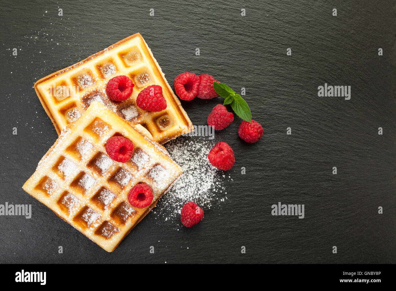 Belgian waffles with raspberries and powdered sugar on black slate platter, top view - Stock Image