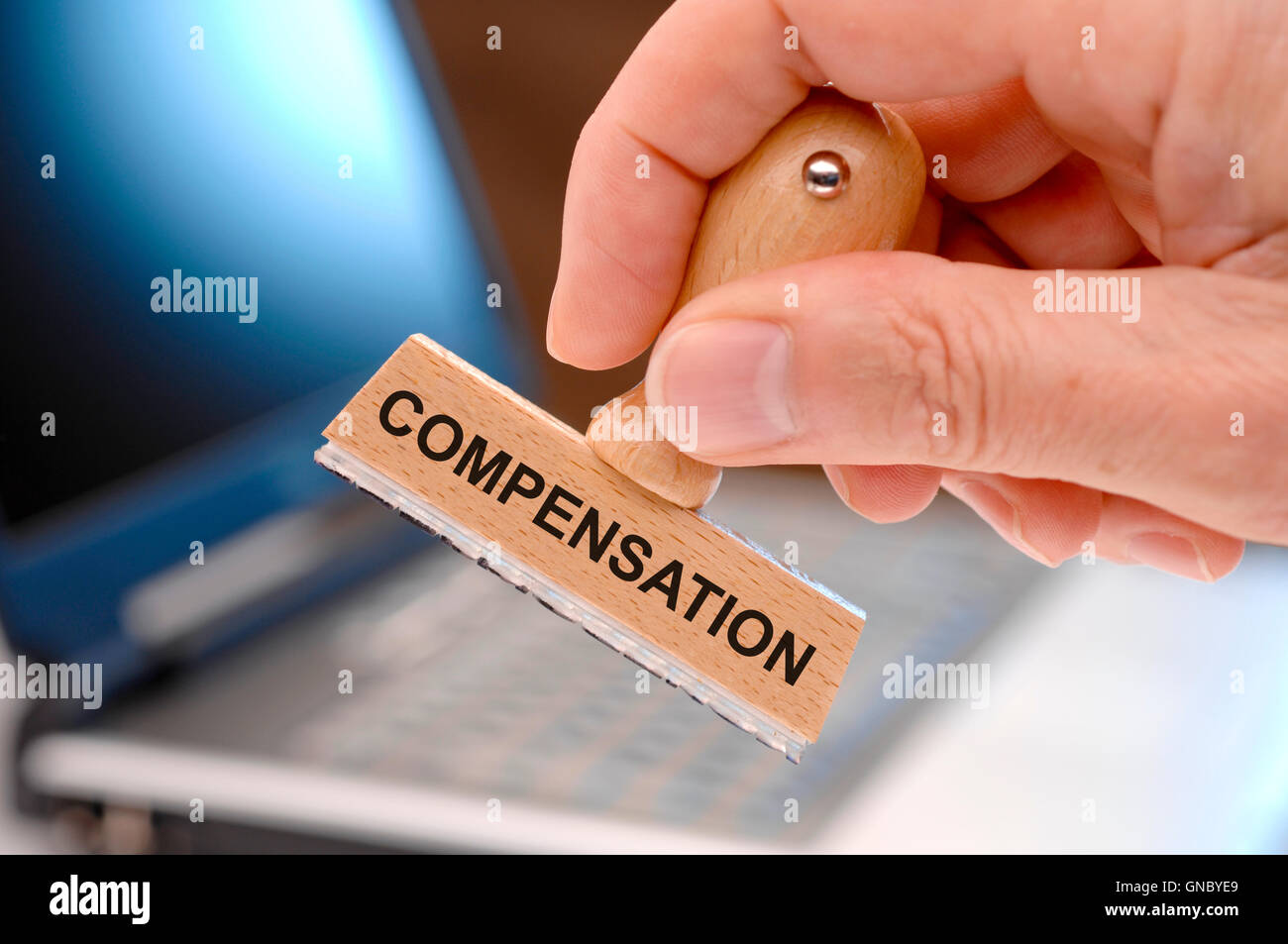 rubber stamp in hand and compensation printed on it Stock Photo