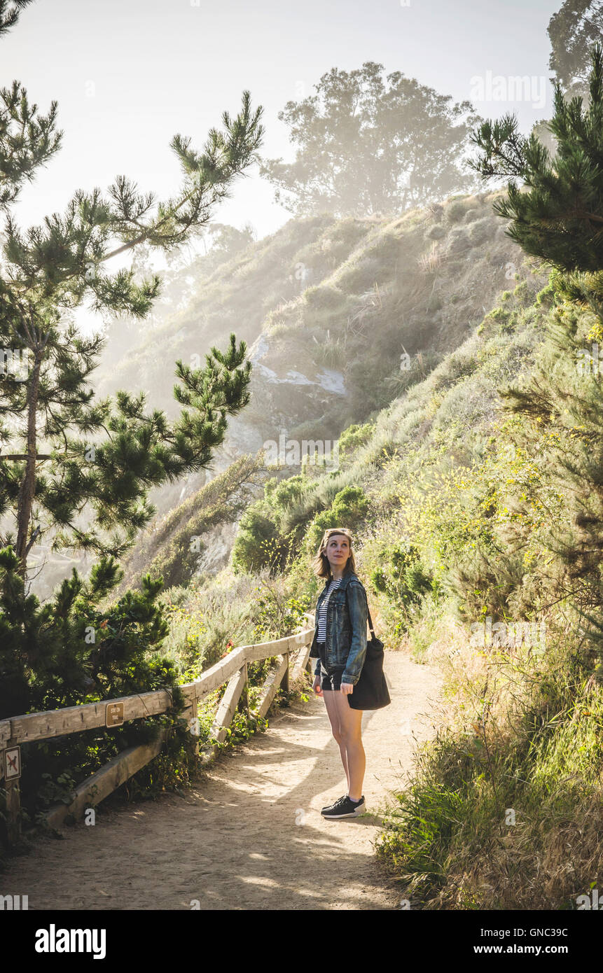 Young Woman Stopping Along Path, McWay Cove, Big Sur, California, USA - Stock Image
