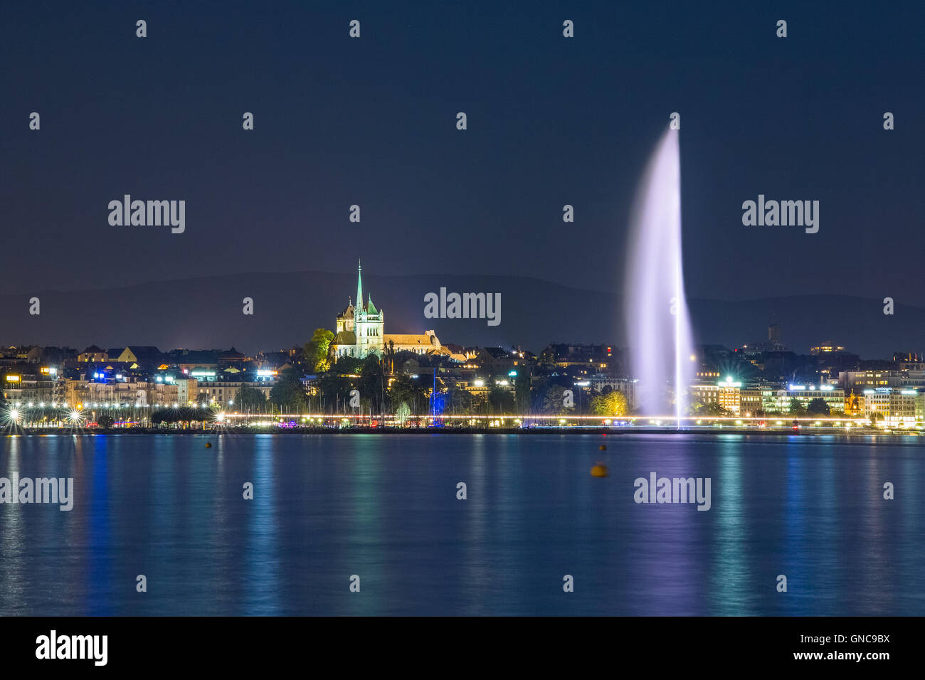 Geneva skyline and fountain at night. - Stock Image