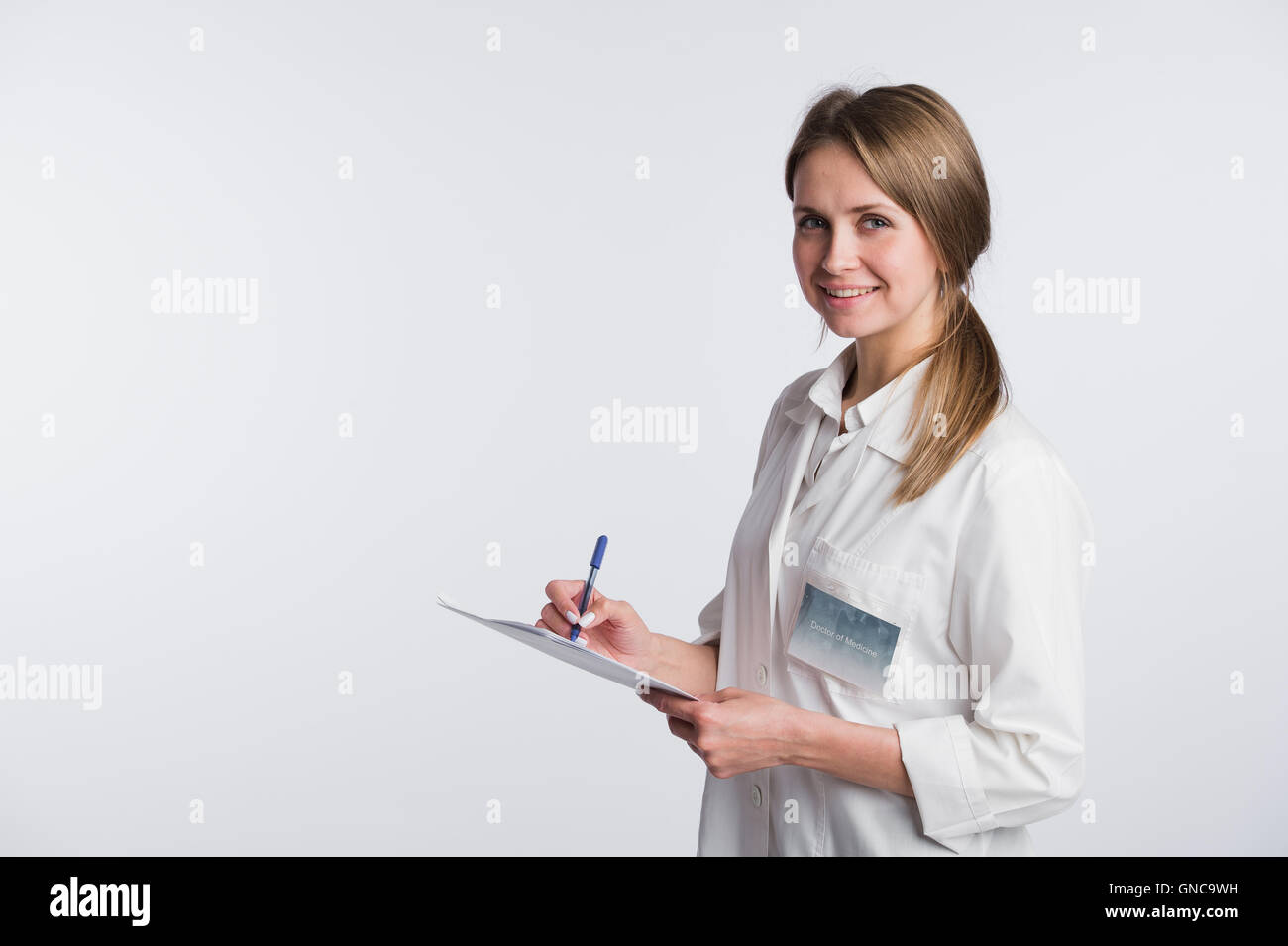 Cheerful medical doctor woman taking notes. Isolated on white - Stock Image