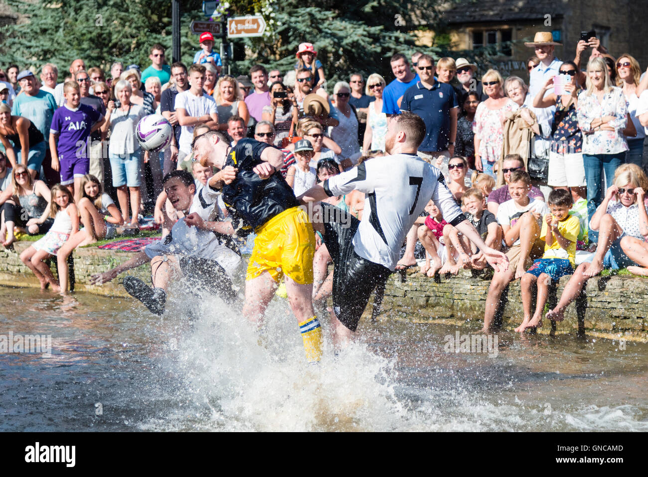 Football game in the river at Bourton-on-the-Water, Cotswolds, UK. - Stock Image