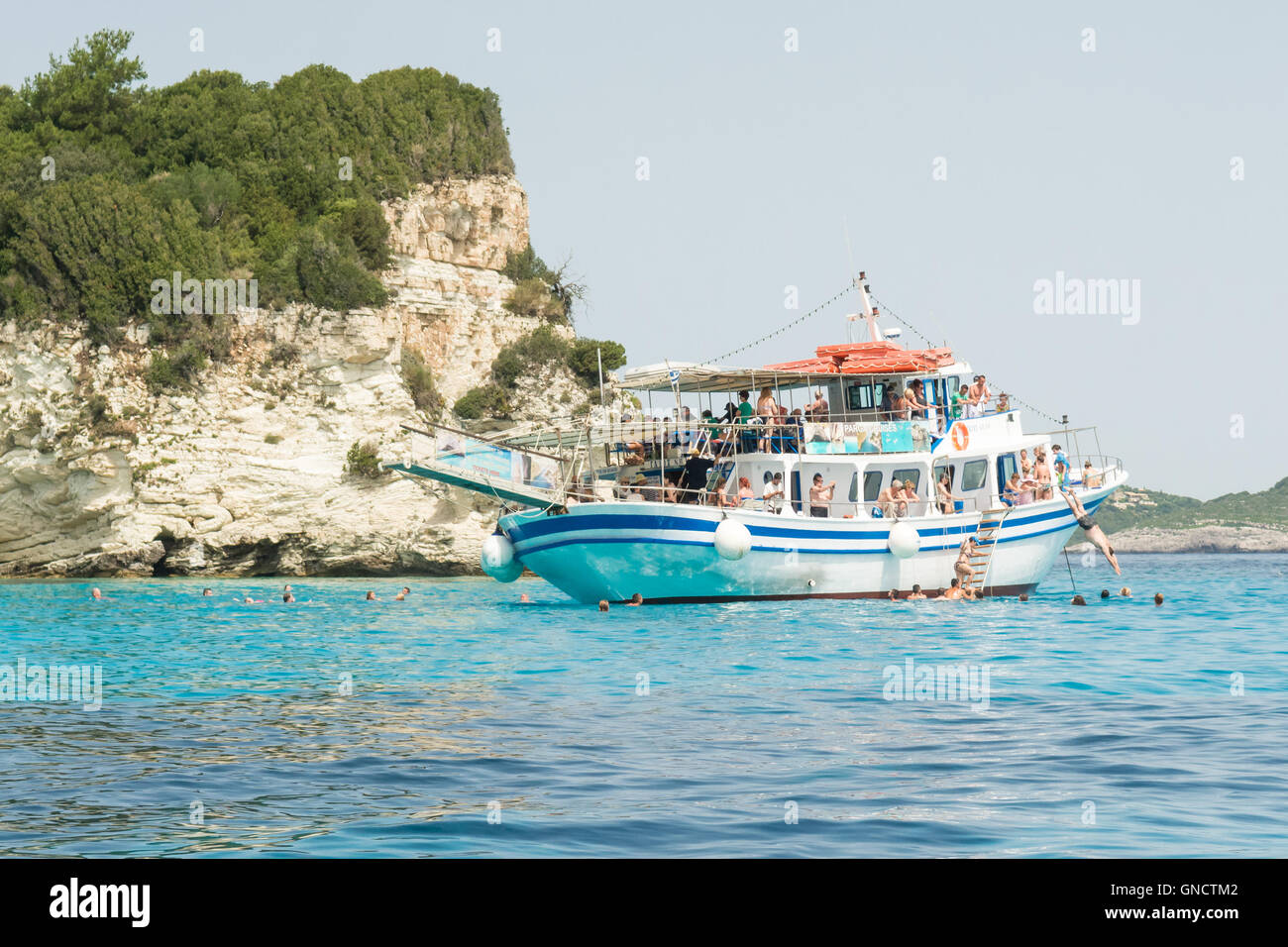 Tourists on a day trip from nearby Corfu swimming in the sea from a cruise boat moored off the tiny Ionian island - Stock Image
